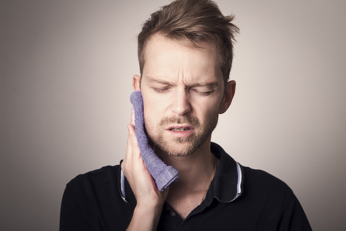 man holding cold towel to his right cheek with clear tooth pain
