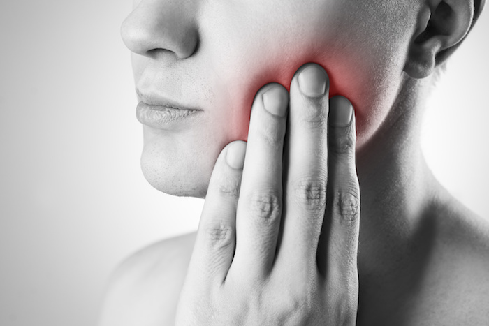 woman touching her chin with red highlighting the pain in her mouth